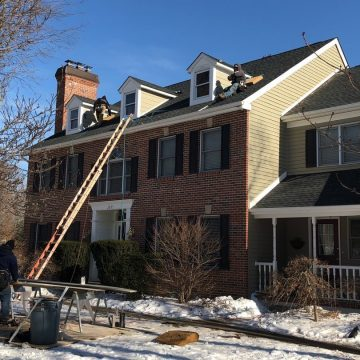ladders against the roof as workers climb up to install shingles