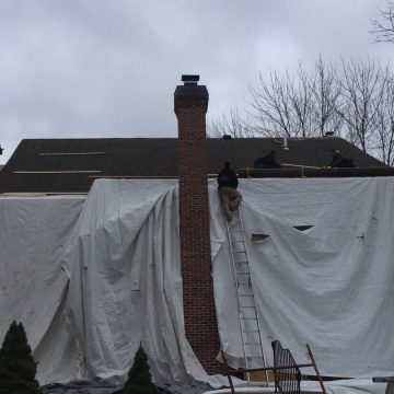 drop cloth over back of house during roofing project