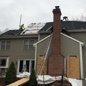 Roofers working on the roof while installing new shingles