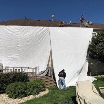 Protecting the house with a sheet before removing shingles