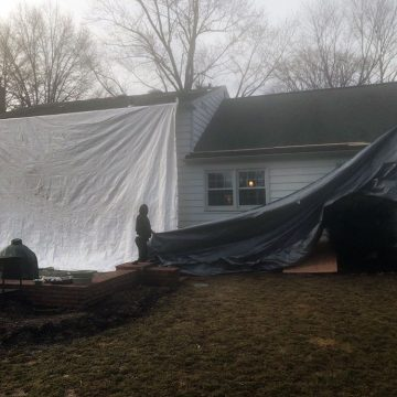 Protecting home with a protective cloth before starting shingle removal