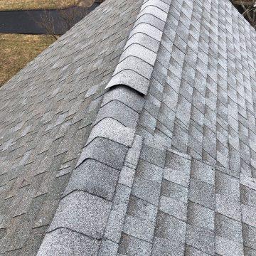 Loose shingles at the top of the roof