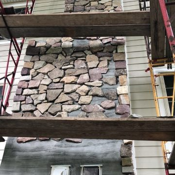 We carefully begin working on a new stone wrapped chimney.